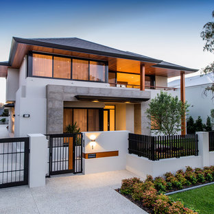 This is an example of a large contemporary two-storey stucco white exterior in Perth with a hip roof.