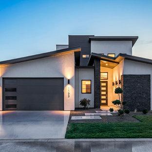 Пример оригинального дизайна: серый, большой, двухэтажный частный загородный дом в современном стиле с односкатной крышей, комбинированной облицовкой и зеленой крышей