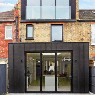 Ejemplo de fachada de casa pareada beige, actual, de tamaño medio, de tres plantas, con revestimiento de metal y tejado plano
