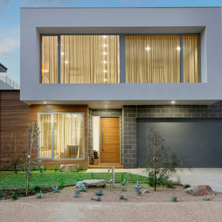This is an example of a contemporary two-storey grey house exterior in Melbourne with mixed siding and a flat roof.