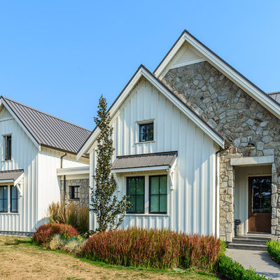 Large cottage white two-story concrete fiberboard exterior home photo in Vancouver with a metal roof