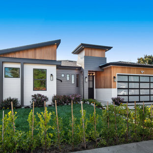 Large contemporary multicolored one-story mixed siding house exterior idea in Los Angeles with a shed roof and a shingle roof