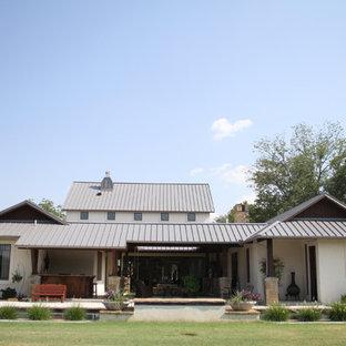 Foto de fachada blanca, ecléctica, grande, de dos plantas, con revestimiento de estuco y tejado a dos aguas