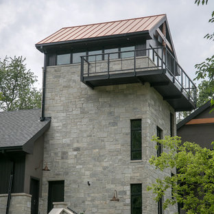 Example of a large trendy black three-story mixed siding exterior home design in Milwaukee with a mixed material roof