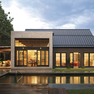 Large contemporary beige one-story mixed siding gable roof idea in Denver