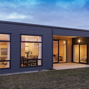 Inspiration for a small scandinavian gray one-story concrete fiberboard exterior home remodel in Christchurch with a metal roof