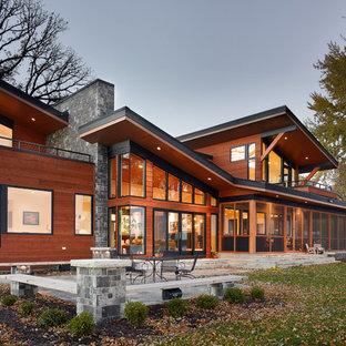 Diseño de fachada de casa marrón, actual, grande, de dos plantas, con revestimiento de madera y tejado plano