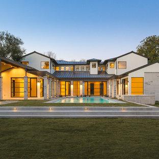 Foto de fachada de casa gris, actual, de tamaño medio, de dos plantas, con revestimiento de piedra, tejado a dos aguas y tejado de metal