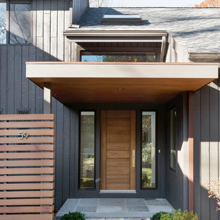 Mid-sized trendy black two-story wood exterior home photo in New York with a shed roof