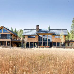 Foto de fachada de casa marrón, minimalista, grande, de dos plantas, con revestimientos combinados y tejado a dos aguas