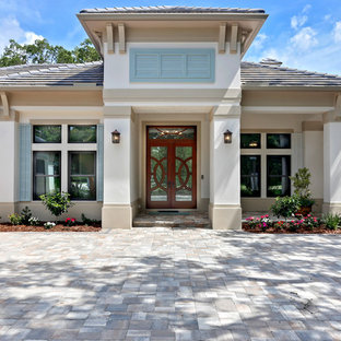 Inspiration for a large transitional beige one-story stucco exterior home remodel in Tampa with a shingle roof