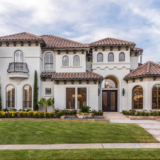 Example of a large tuscan beige two-story stucco exterior home design in Dallas with a hip roof and a tile roof