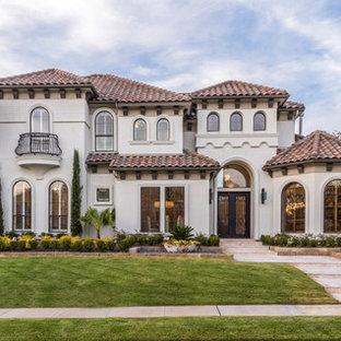 Ejemplo de fachada de casa beige, mediterránea, grande, de dos plantas, con tejado a cuatro aguas, tejado de teja de barro y revestimiento de estuco
