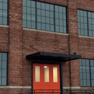 Esempio della facciata di un appartamento industriale a tre o più piani con rivestimento in mattoni, tetto piano e copertura mista