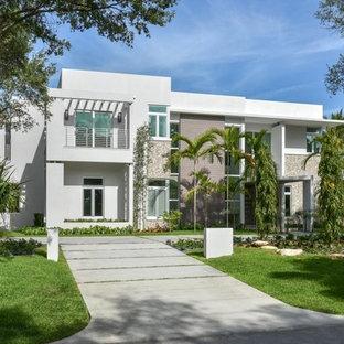 Пример оригинального дизайна: большой, двухэтажный, белый многоквартирный дом в стиле модернизм с комбинированной облицовкой и плоской крышей
