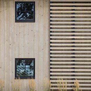 Ispirazione per la facciata di una casa ampia marrone country a due piani con rivestimento in legno e tetto a capanna