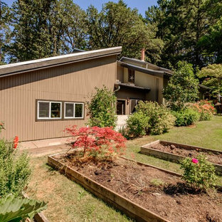 Example of a huge 1950s split-level house exterior design in Portland with a metal roof