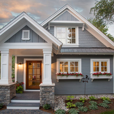 Gray two-story concrete fiberboard house exterior photo in Other with a mixed material roof