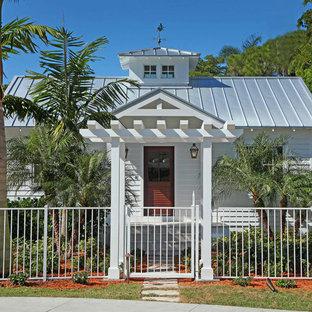 Cette photo montre une façade en bois blanche exotique de plain-pied et de taille moyenne avec un toit à deux pans et un toit en métal.