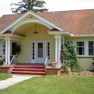Неиссякаемый источник вдохновения для домашнего уюта: маленький, одноэтажный, желтый дом в стиле шебби-шик с облицовкой из цементной штукатурки и двускатной крышей