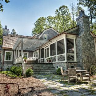 Пример оригинального дизайна интерьера: двухэтажный фасад частного дома среднего размера серого цвета в викторианском стиле с облицовкой из дерева, мансардной крышей и крышей из гибкой черепицы
