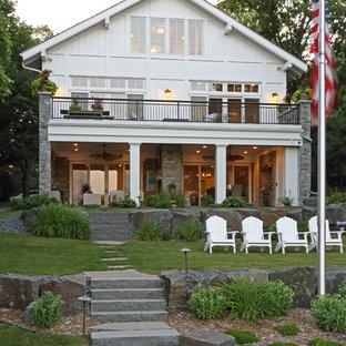 Diseño de fachada de casa blanca, marinera, de tamaño medio, de dos plantas, con revestimiento de madera y tejado de teja de madera