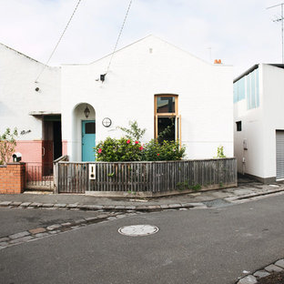 Mid-sized eclectic white two-story brick exterior home photo in Melbourne with a shed roof