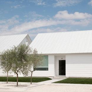 Стильный дизайн: одноэтажный, белый дом среднего размера в современном стиле с двускатной крышей, облицовкой из винила и белой крышей - последний тренд