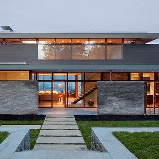 Modern inredning av ett mellanstort hus, med platt tak, två våningar och glasfasad