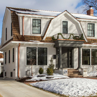 Elegant white two-story stucco exterior home photo in Minneapolis with a gambrel roof