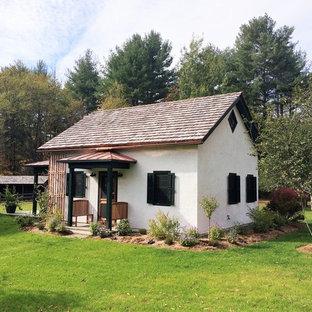 Imagen de fachada blanca, de estilo de casa de campo, de tamaño medio, de una planta, con revestimiento de estuco y tejado a dos aguas