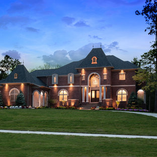 Huge french country red two-story brick house exterior photo in Cincinnati with a hip roof and a shingle roof