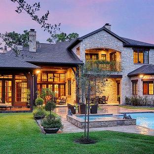Large elegant gray two-story stone gable roof photo in Houston
