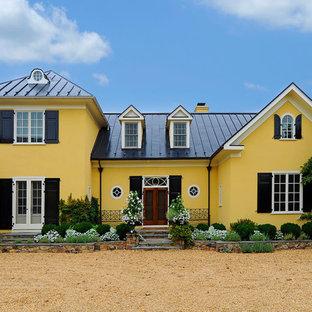 Ejemplo de fachada amarilla, clásica, de dos plantas