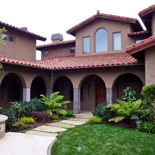 Modelo de fachada marrón, vintage, grande, de dos plantas, con revestimiento de adobe y tejado a dos aguas
