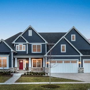 Réalisation d'une grand façade de maison bleue tradition à un étage avec un revêtement en panneau de béton fibré, un toit en shingle et un toit à quatre pans.