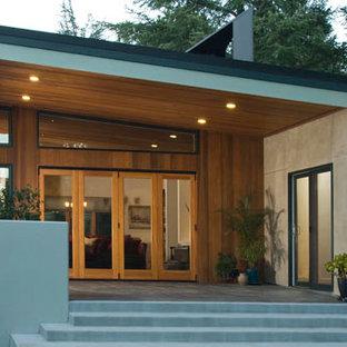 Immagine della facciata di una casa grande multicolore moderna a un piano con rivestimenti misti e tetto a una falda