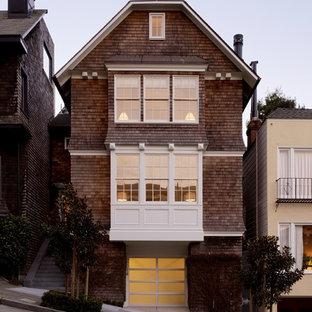 Imagen de fachada de casa pareada clásica, grande, de tres plantas, con revestimiento de madera y tejado a la holandesa