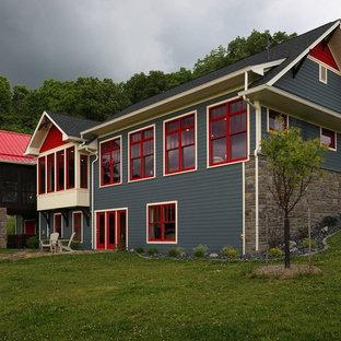 Imagen de fachada de casa azul, de estilo americano, grande, a niveles, con revestimiento de madera y tejado a dos aguas