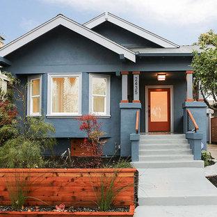 На фото: одноэтажный, синий частный загородный дом в стиле кантри с двускатной крышей и облицовкой из цементной штукатурки с