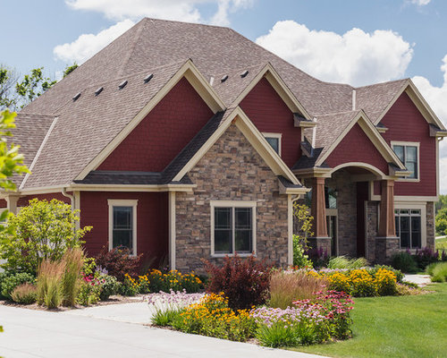 large arts and crafts red mixed siding exterior home photo in milwaukee with a shingle roof