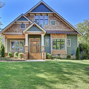 Cette image montre une façade de maison verte craftsman à un étage et de taille moyenne avec un revêtement mixte et un toit à deux pans.