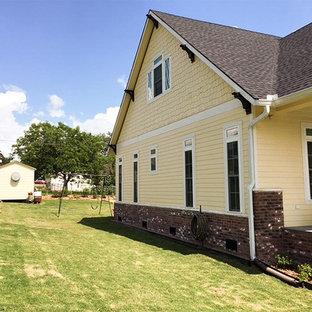 Modelo de fachada de casa amarilla, de estilo americano, de una planta, con revestimiento de madera, tejado a dos aguas y tejado de teja de madera