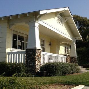 Aménagement d'une façade en bois jaune craftsman de taille moyenne et de plain-pied avec un toit à deux pans.