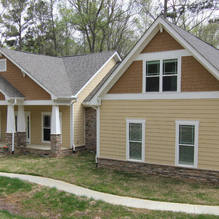 Large arts and crafts brown two-story mixed siding exterior home photo in Raleigh with a hip roof