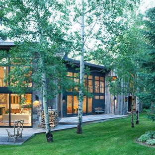 Inspiration för ett stort funkis grått trähus, med två våningar och pulpettak