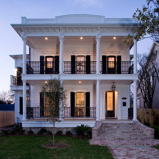 Large traditional white two-story wood house exterior idea in Houston