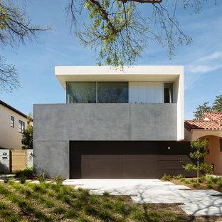Imagen de fachada de casa beige, contemporánea, de dos plantas, con tejado plano y revestimiento de hormigón