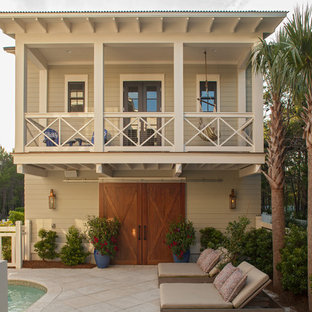 Example of a coastal two-story wood exterior home design in Miami