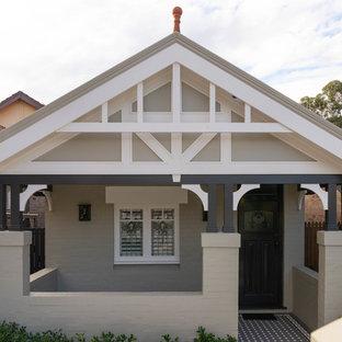 Ejemplo de fachada de casa pareada beige, pequeña, de dos plantas, con revestimiento de ladrillo, tejado a dos aguas y tejado de teja de barro